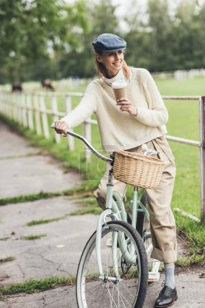 woman with coffee on bicycle