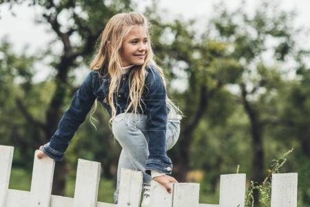 Photo for Spring blonde child climbing over the fence at countryside - Royalty Free Image