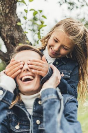 daughter making surprise to mother