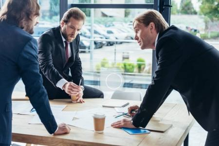 Photo for Three confident professional businessmen working with papers in office - Royalty Free Image