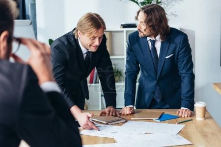 Photo pour Milieu professionnel hommes âgés formal wear discuter des documents au bureau - image libre de droit