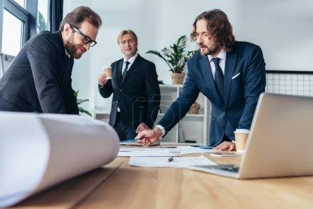 Photo pour Professionnels moyens âgés hommes d'affaires discuter des documents au bureau - image libre de droit