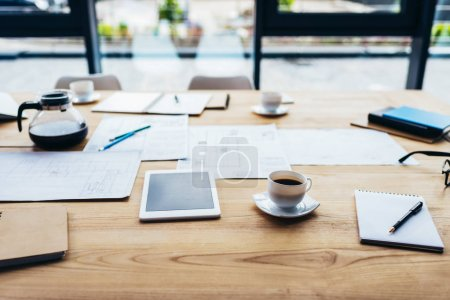Photo for Close-up view of digital tablet with blank screen, coffee and papers on table - Royalty Free Image
