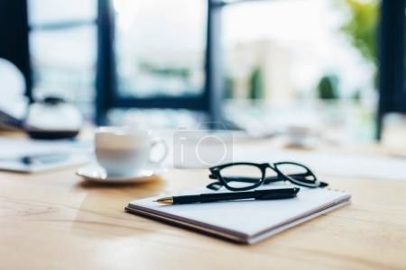 Photo for Close-up view of eyeglasses with notebook and pen on wooden table - Royalty Free Image