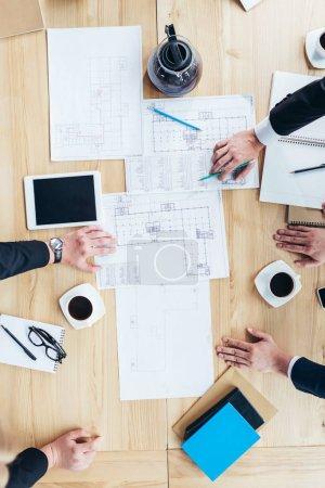 Businessmen working with blueprints