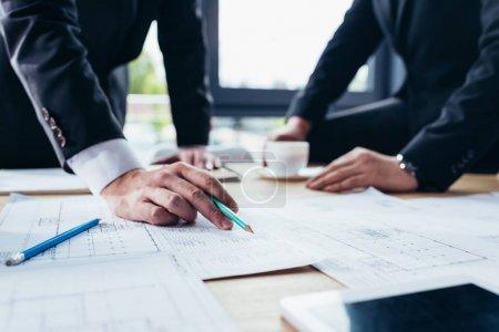 Photo pour Recadrée tir des hommes d'affaires travaillant avec les bleus au bureau - image libre de droit