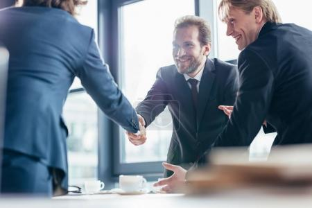 Photo for Cheerful professional middle aged businessmen shaking hands in office - Royalty Free Image