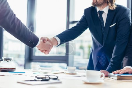 Photo for Cropped shot of professional businessmen in formal wear shaking hands in office - Royalty Free Image