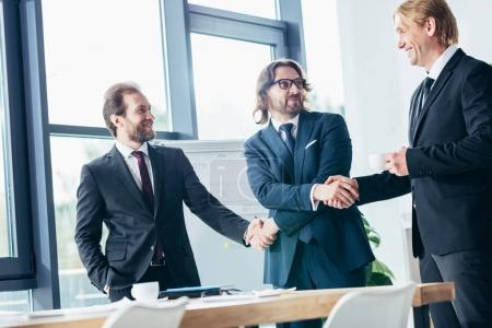 Photo pour Professionnel souriant middle âgés hommes d'affaires se serrant la main au bureau - image libre de droit