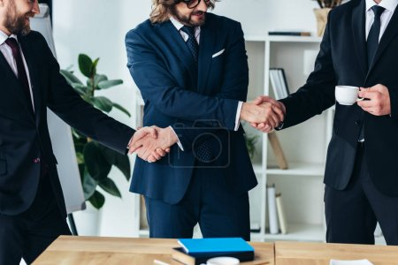 Photo for Cropped shot of three professional businessmen shaking hands in office - Royalty Free Image