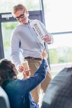 Photo pour Hommes d'affaires détenant des journaux et le café tout en parlant au bureau - image libre de droit