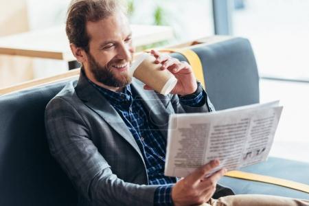 Photo pour Beau souriant homme d'âge moyen lire le journal et boire du café dans le café - image libre de droit