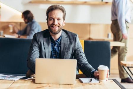 Photo pour Bel homme barbu à l'aide d'ordinateur portable et souriant à la caméra tout en buvant du café au café - image libre de droit
