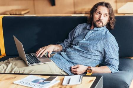 Photo for Bearded middle aged man using laptop and looking away - Royalty Free Image