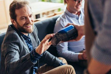 Photo pour Souriant barbu client payer facture par terminal de paiement tandis que le serveur dispositif de maintien - image libre de droit