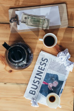 Coffee, money and newspaper on table