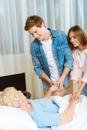 Couple visiting sick senior woman