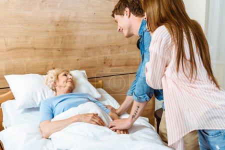 Photo for Young smiling couple holding hands of an elderly woman lying in hospital bed - Royalty Free Image