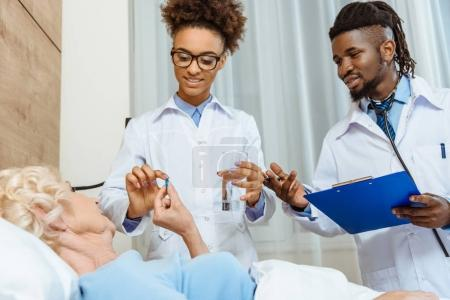 Doctors handing sick woman medicine