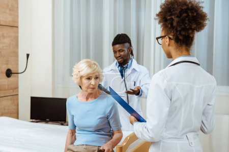 Elderly woman with doctors in hospital
