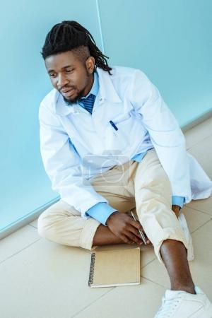 Doctor sitting on hospital floor