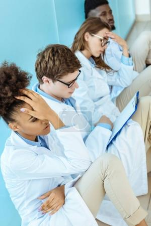 Photo for Four young medical interns in white robes sitting on a floor in hospital corridor looking troubled - Royalty Free Image