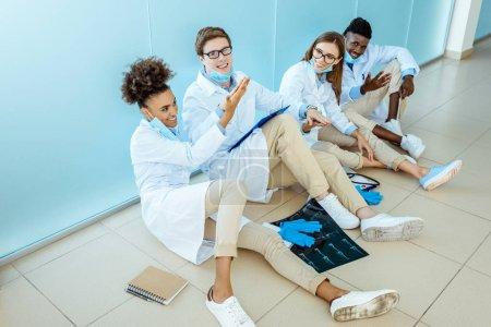 Photo pour Quatre souriant jeunes stagiaires médicaux en robes blanches, assis sur un sol en haute fiving hôpital et célébrer les succès - image libre de droit