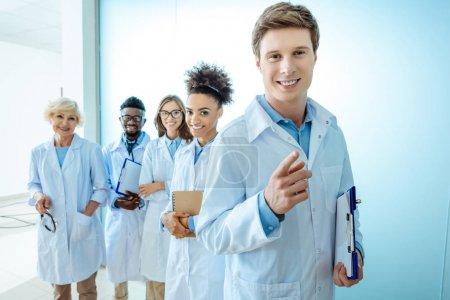 Photo pour Groupe multiracial de stagiaires médicaux souriants en blouse de laboratoire debout dans une rangée avec presse-papiers et stéthoscopes - image libre de droit