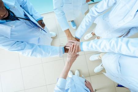 Photo for Partial view of multiracial group of doctors in lab coats holding hands, teamwork concept - Royalty Free Image