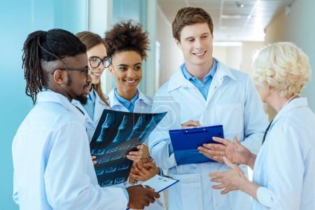 Photo pour Un groupe multiracial de jeunes stagiaires en médecine écoutant un médecin aîné dans un couloir d'hôpital - image libre de droit