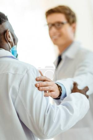 doctor patting colleague on shoulder