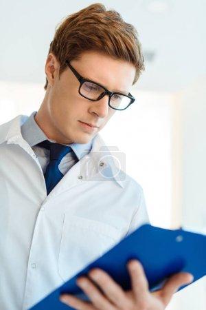 Photo pour Jeune médecin en blouse de laboratoire et lunettes regardant les notes sur le presse-papiers - image libre de droit