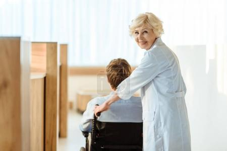 Doctor rolling wheelchair with patient