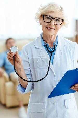 Photo for Senior doctor smiling cheerfully and holding stethoscope and clipboard - Royalty Free Image