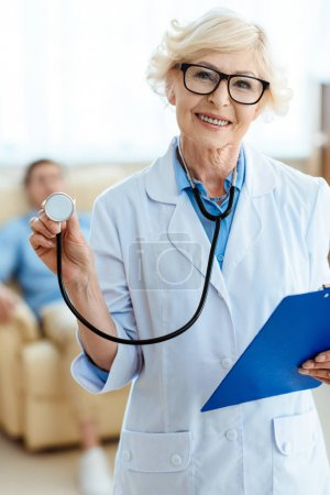Senior doctor with stethoscope and clipboard