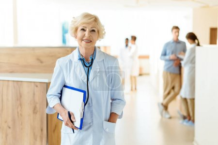 Photo for Senior doctor in lab coat standing in hospital hall and holding a clipboard - Royalty Free Image