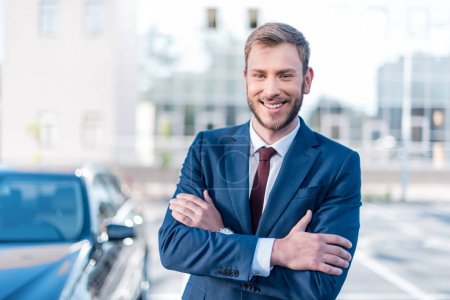 Photo for Young smiling businessman in suit with crossed arms standing at car on parking - Royalty Free Image