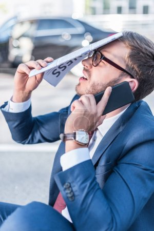 stressed businessman with newspaper and smartphone