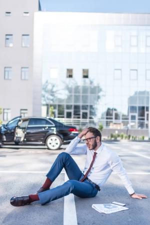 Stressed businessman sitting on parking