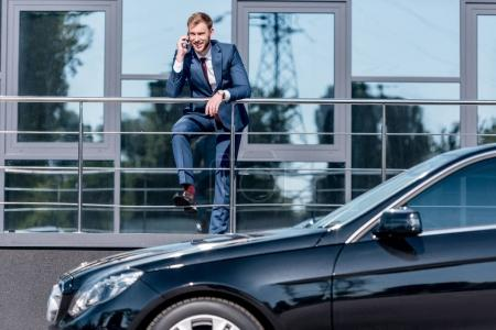 Businessman at office building and car