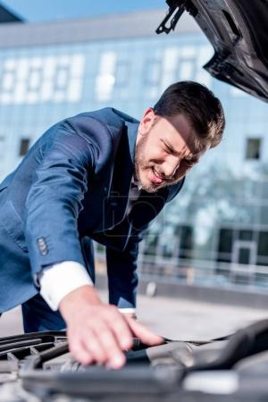 businessman repairing car