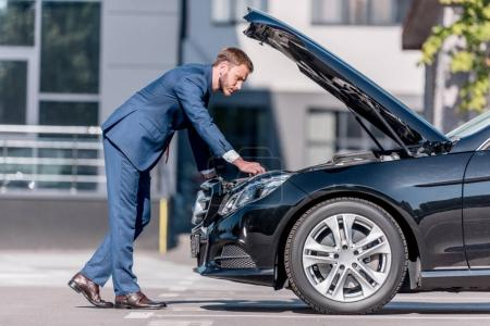Photo for Stylish businessman in suit repairing car at office building - Royalty Free Image