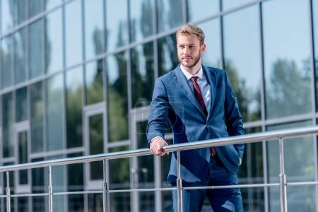 Photo for Stylish businessman in suit standing at office building - Royalty Free Image