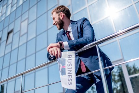 businessman with newspaper at office building