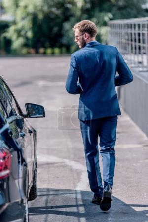 Businessman in suit at car