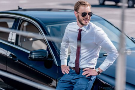Businessman in suit at car