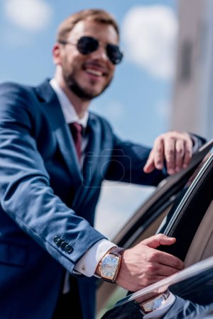 businessman standing at car