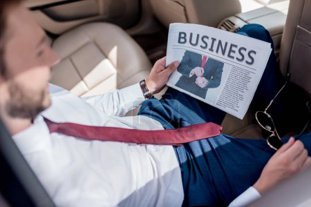man with business newspaper on backseat of car