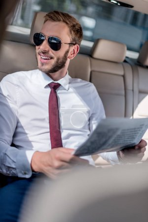 businessman with newspaper on backseat of car