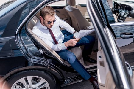 Businessman with newspaper on backseat